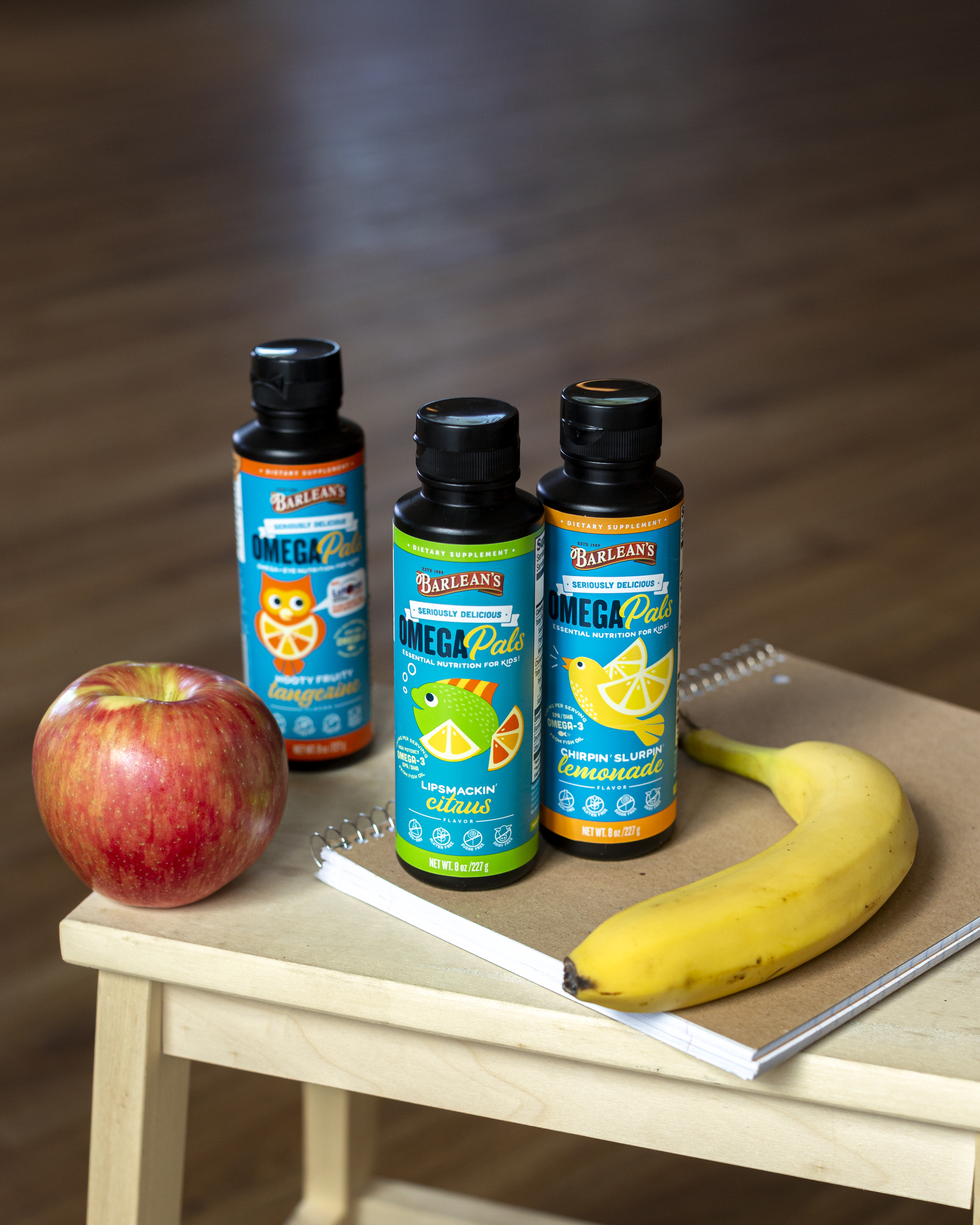 Three bottles of Seriously Delicious Omega Pals with on top of a notebook with an apple and banana next to them.